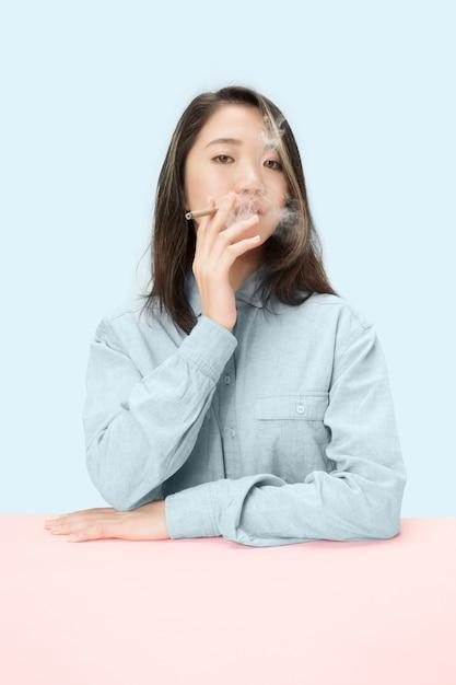 Jeunes Femmes Coréennes Fumant Un Cigare Assis à Table Au Studio. Photo gratuit