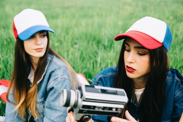 Jeunes femmes dans le champ de l'été assis dans des chapeaux colorés Photo gratuit