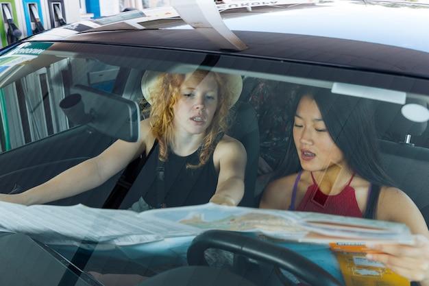 Jeunes femmes discutant de manière en voiture Photo gratuit