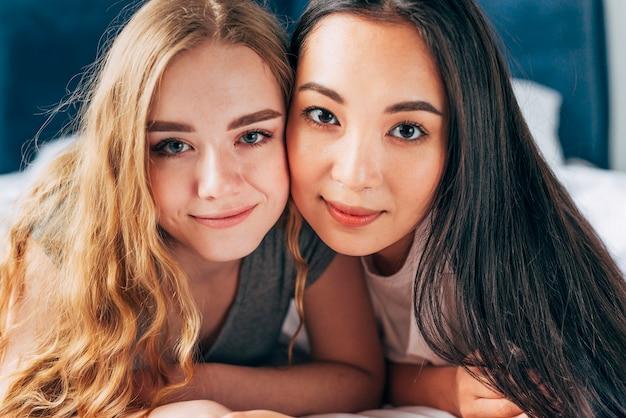 Jeunes femmes étreignant et regardant la caméra Photo gratuit