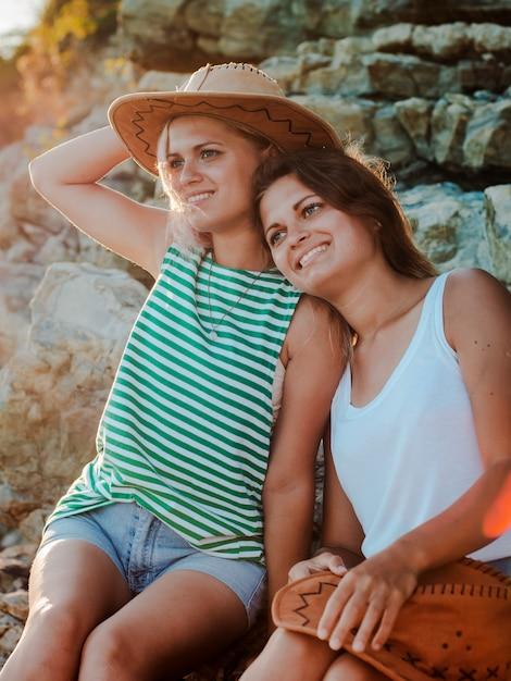 Jeunes femmes gaies dans des chapeaux hipsters sur un rocher sur la côte de la mer. Photo Premium