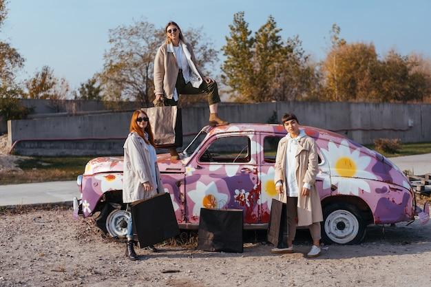 Jeunes Femmes Heureuses Avec Des Sacs Posant Près D'une Vieille Voiture Décorée Photo gratuit