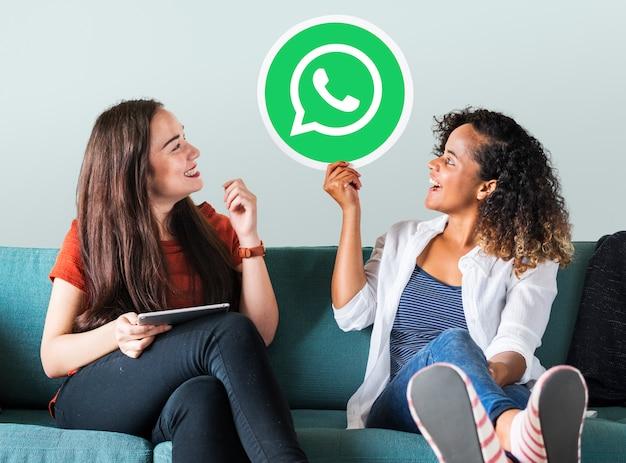 Jeunes femmes montrant une icône whatsapp messenger Photo gratuit