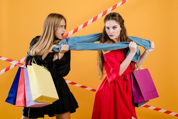 Jeunes femmes portant des robes se disputant une paire de jeans avec des sacs isolés sur jaune Photo Premium