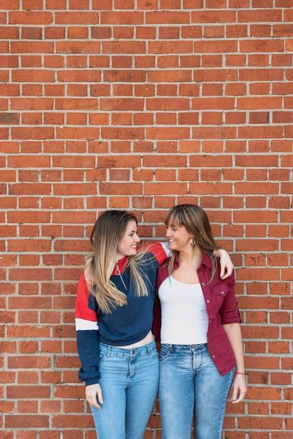Jeunes femmes posant avec mur de briques Photo gratuit