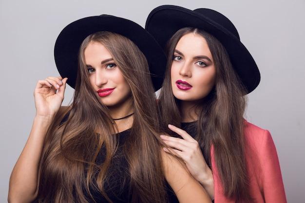 Jeunes Femmes Posant Et Portant Des Chapeaux Noirs élégants Photo gratuit