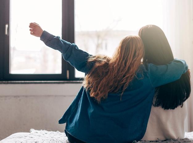 Jeunes femmes regardant par la fenêtre Photo gratuit