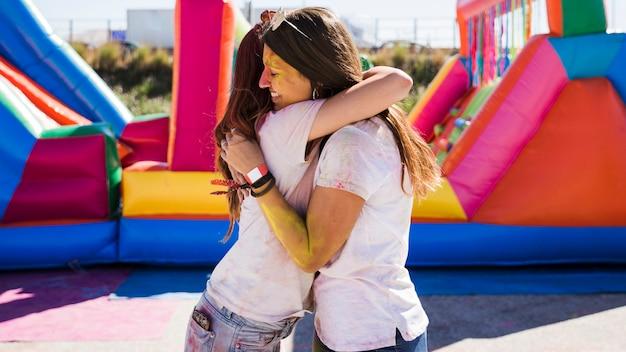 Jeunes femmes s'embrassant pour célébrer le festival de holi Photo gratuit