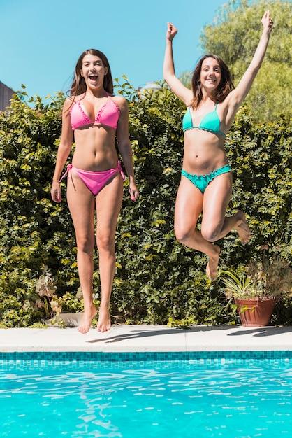 Jeunes femmes sautant au bord de la piscine Photo gratuit