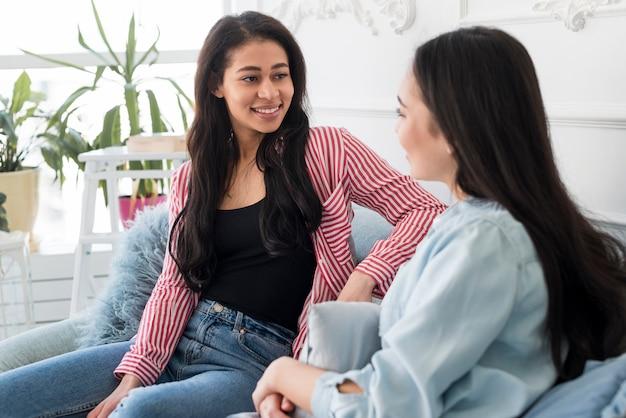 Des jeunes femmes souriantes communiquent à la maison Photo gratuit