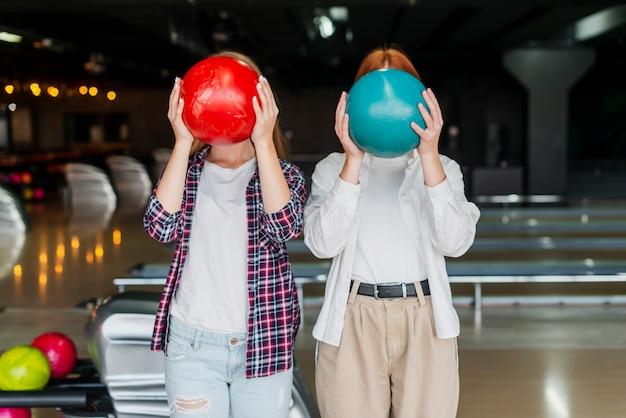 Jeunes Femmes Tenant Des Boules De Bowling Colorées Photo gratuit