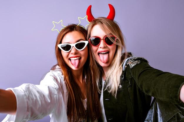 Jeunes Filles Drôles Faisant Selfie, Lunettes Vintage, Bandeaux De Fête Diable Et étoiles, Vêtements De Jeunesse Décontractés, Humeur Positive. Photo gratuit