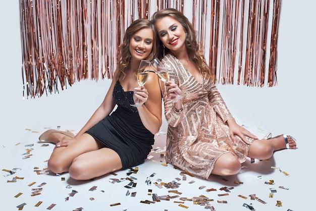 Jeunes Filles élégantes S'amusant Et Buvant Du Champagne Lors De La Fête Du Nouvel An. Photo Premium