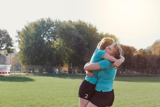 Jeunes footballeurs s'embrassant Photo gratuit