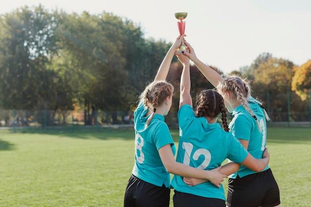 Jeunes footballeurs soulevant un trophée Photo gratuit
