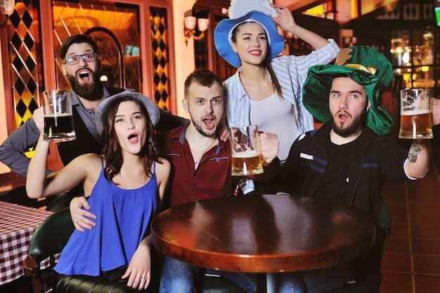 Jeunes gars et filles tenant des verres de bière, regarder le football, rire et sourire Photo Premium