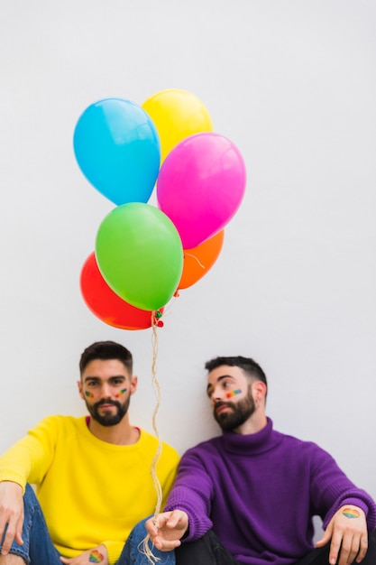 Jeunes gays assis avec des ballons colorés Photo gratuit