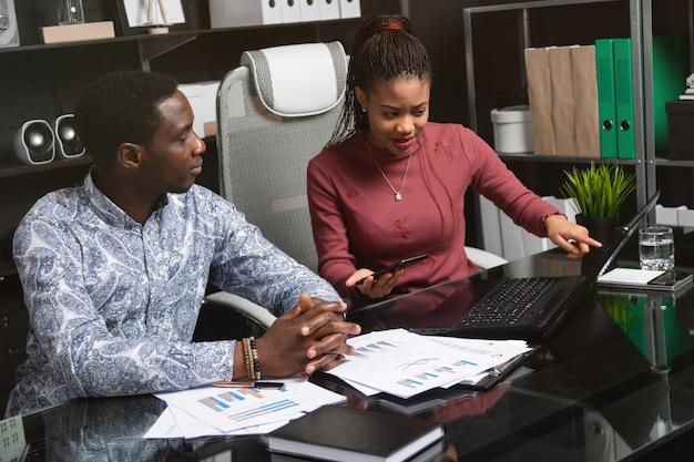 Jeunes gens d'affaires de nationalité afro-américaine travaillant avec des documents et par téléphone Photo Premium