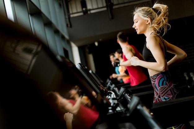 Jeunes gens courir sur des tapis roulants dans une salle de sport moderne Photo Premium