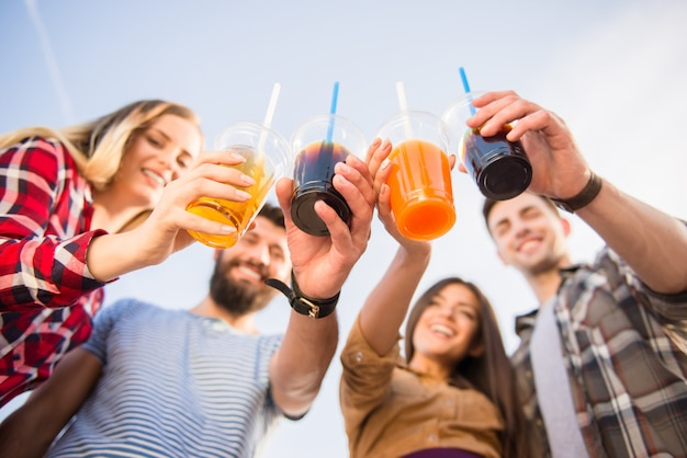 Les jeunes gens heureux boivent des boissons. Photo Premium