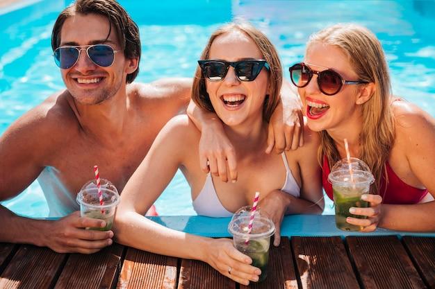 Jeunes gens riant dans la piscine Photo gratuit