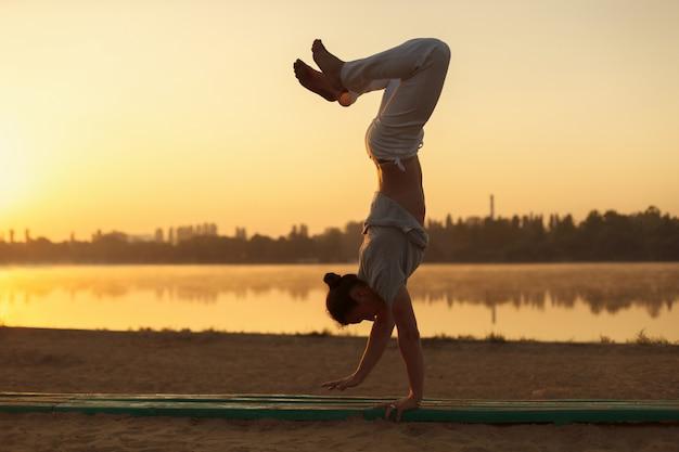 Les Jeunes Hommes Athlétiques Debout Dans La Pose De Yoga Sur Près Du Lac Dans Le Parc Photo gratuit
