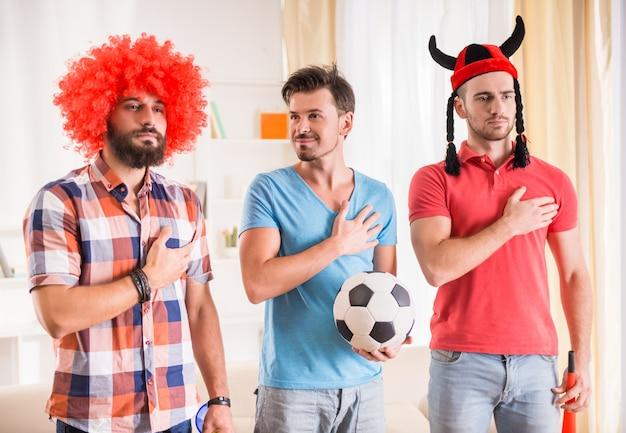 Les jeunes hommes boivent de la bière, mangent des pizzas et encouragent le football Photo Premium