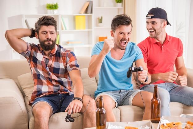 Jeunes hommes boivent de la bière, mangent des pizzas et jouent à des jeux Photo Premium