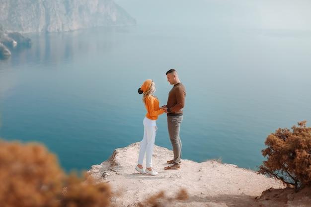 Les Jeunes Hommes Et Une Femme Se Tiennent Au Sommet D'une Montagne Avec Vue Panoramique Sur La Baie De La Mer Photo Premium