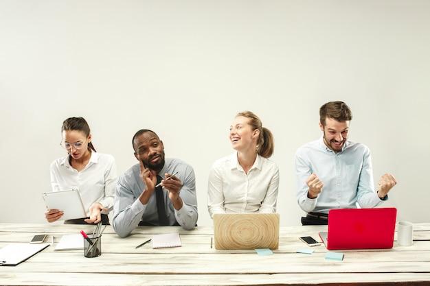 Jeunes Hommes Et Femmes Assis Au Bureau Et Travaillant Sur Des Ordinateurs Portables. Concept D'émotions Photo gratuit