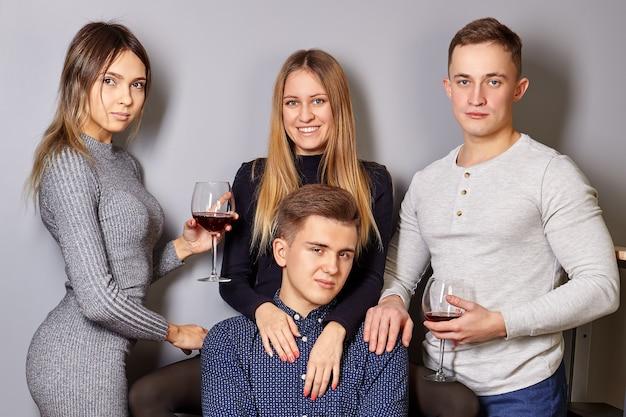 Les Jeunes Hommes Et Femmes, Avec Des Verres De Vin Dans Leurs Mains, Font Un Portrait De Groupe Après La Fête. Photo Premium