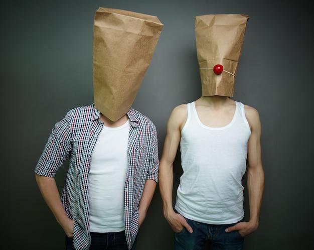 Les jeunes hommes avec des sacs en papier sur la tête Photo gratuit