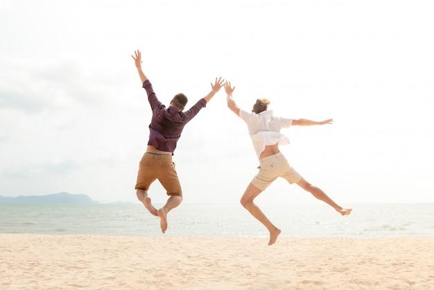 Jeunes hommes de tourisme joyeux énergique sautant à la plage Photo Premium
