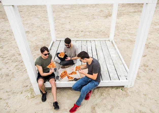 Jeunes hommes en train de manger une pizza sur la plage Photo gratuit