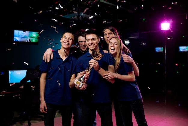 Jeunes Joueurs Excités Dans Les Mêmes T-shirts Posant Avec Cybersports Cup Sous La Chute De Confettis Dans Un Club Informatique Photo Premium