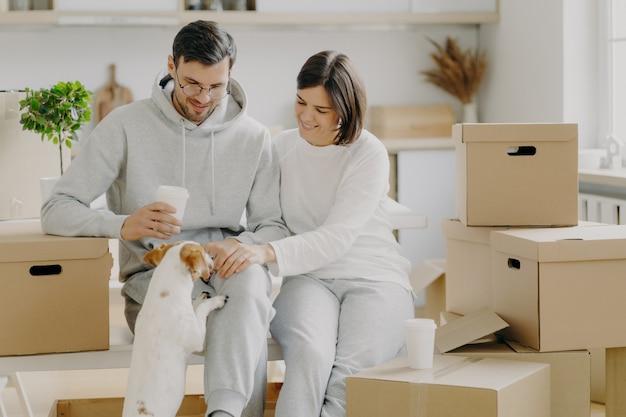 Les jeunes mari et femme sédentaires jouent avec leur chien, s'assoient sur des boîtes en carton, boivent du café à emporter, font une pause le jour du déménagement et défoncent leurs affaires, portent une tenue décontractée, profitent de la vie dans un nouvel appartement. Photo Premium