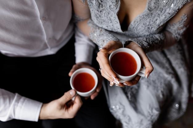 Les jeunes mariés gardent le thé chaud Photo gratuit