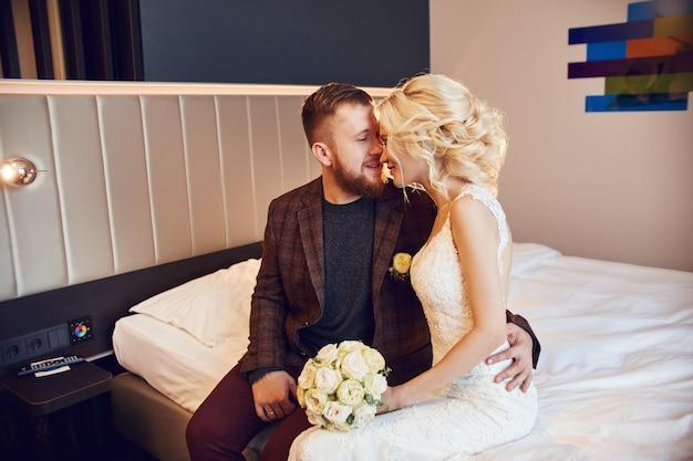 Jeunes mariés le matin dans la chambre d'hôtel Photo Premium