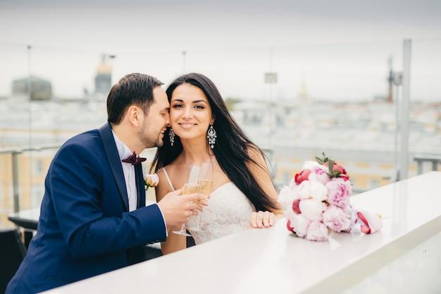 Les jeunes mariés romantiques boivent du champagne, des verres, et sont très heureux de célébrer leur mariage. Photo Premium