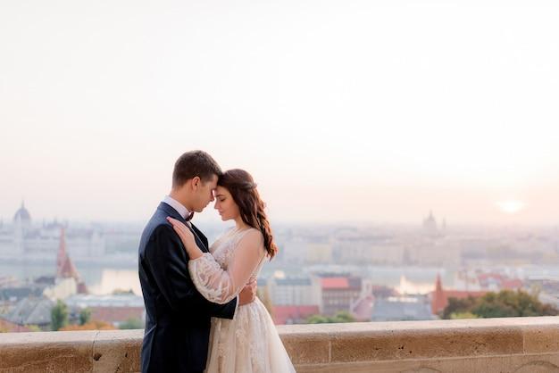 Les Jeunes Mariés Sont Tendres Avec Une Belle Vue Sur Une Grande Ville Dans La Chaude Soirée D'été Photo gratuit
