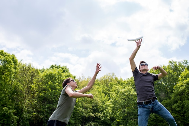 Jeunes mecs jouant au frisbee dans la nature Photo gratuit