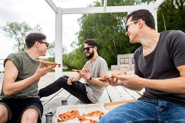 Jeunes mecs avec des morceaux de pizza converser sur la plage Photo gratuit