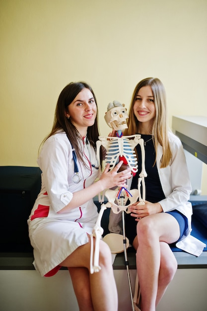 Jeunes médecins s'amusant en posant avec squelette. Photo Premium