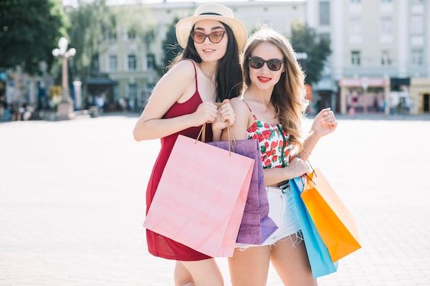 Jeunes modèles confiants avec des sacs en papier brillant Photo gratuit
