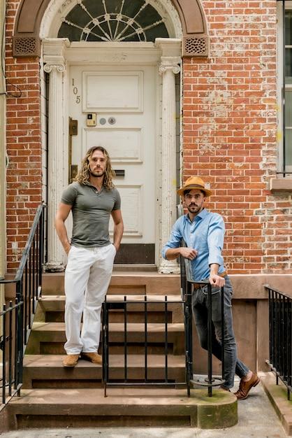 Jeunes modèles masculins posant en plein air dans les escaliers Photo gratuit