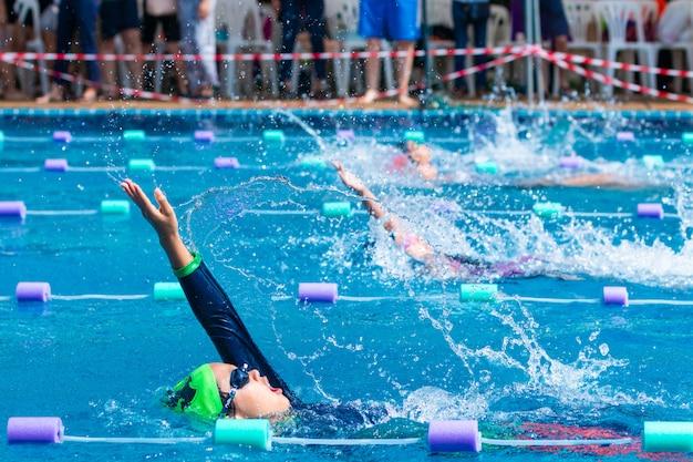 Jeunes nageurs pratiquant la nage en arrière dans une piscine locale Photo Premium