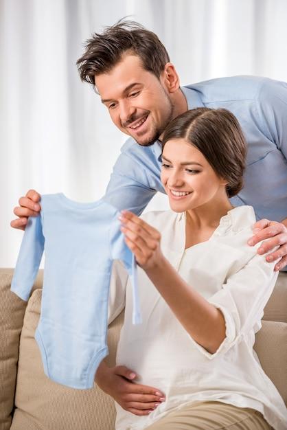 De jeunes parents heureux tiennent les vêtements de leur futur bébé. Photo Premium