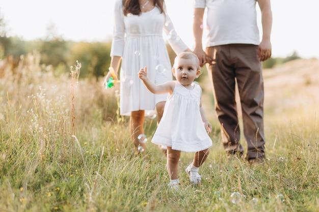 De jeunes parents marchent avec leur jolie petite fille en jean à travers le champ Photo gratuit