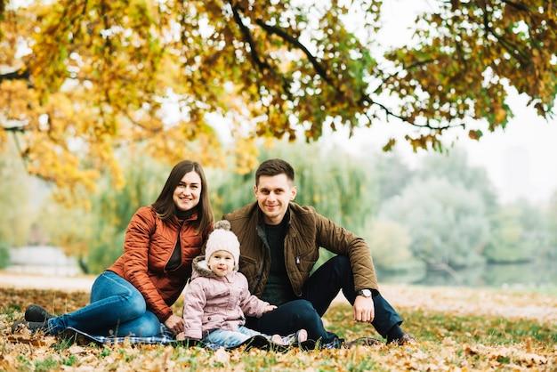 Jeunes parents avec petite fille se reposant dans la forêt d'automne Photo gratuit