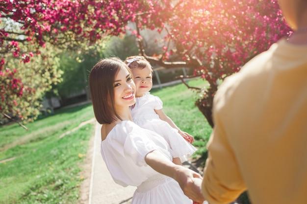 Jeunes Parents Tenant Leur Petite Fille. Famille Heureuse En Plein Air. Mère, Père Et Bébé Mignon S'amuser. Photo Premium